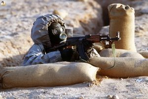 A Syrian soldier aims an AK-47 assault rifle wearing a Soviet-made, model ShMS nuclear–biological–chemical warfare mask.