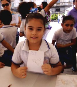Young girl holding a picture of a dove with the word peace written in spanish.