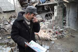 © 2015 Human Rights Watch, A man holds a photograph of his daughter and son-in-law who were killed when a shell struck their garage in Oleksandrivka on 16 January 2015.