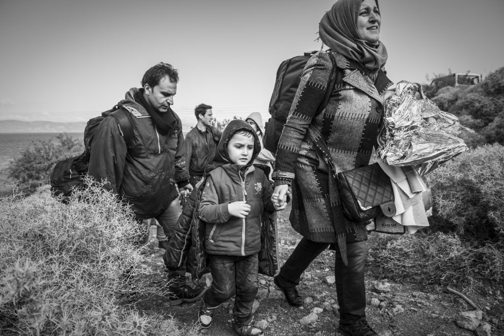 Having just landed in a small boat from Turkey, an Arab family walks up from the beach toward a road on the north coast of the Greek island of Lesbos. They are among more than 500,000 migrants and refugees who have crossed from Turkey to the Greek islands in 2015.