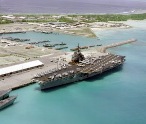 An aerial port bow view of the aircraft carrier USS SARATOGA (CV-60) tied up at pier. This is the first time an aircraft carrier has visited the island.