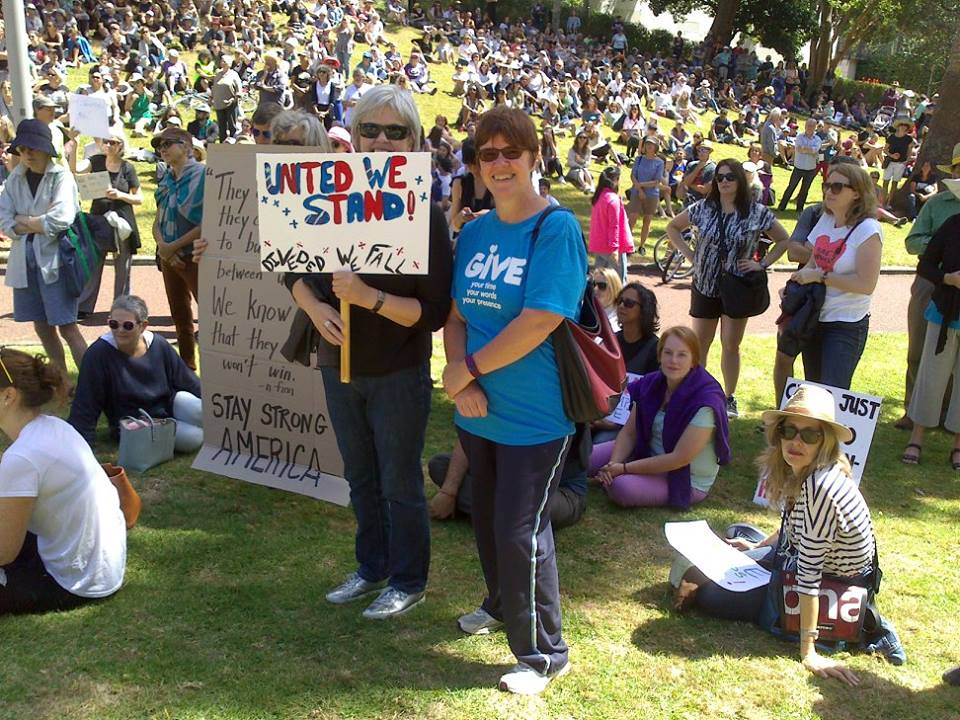Megan Hutching from WILPF New Zealand/Aotearoa holding banner at march in Auckland, New Zealand. Photo: Nola Smith