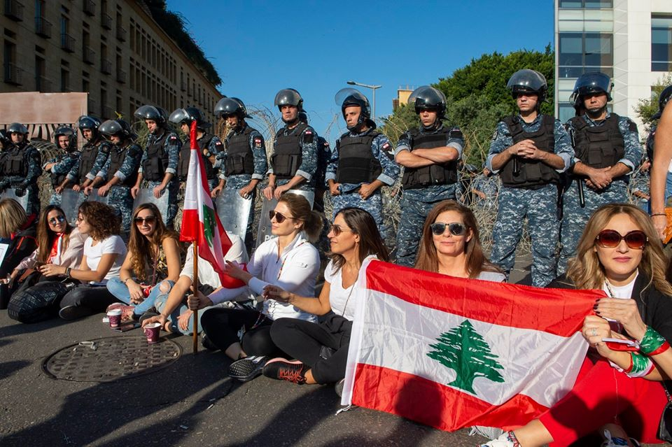 A group of women sitting in a row on the ground, holding the Lebanese flag. And soldiers are standing behind them