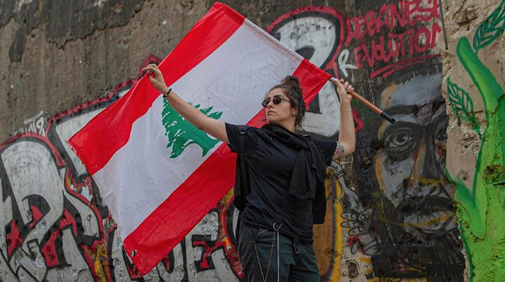 Arab woman holding the Lebanese flag and standing in front of a colorful mural