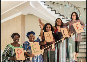"""front cover of annual report showing five women on a staircase each holding a letter of the word PEACE. The title says """"Stories of Feminist Peace"""" with the date 2019"""
