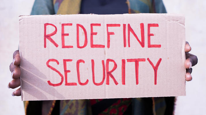 """Woman holding a sign reading """"Redefine Security""""."""