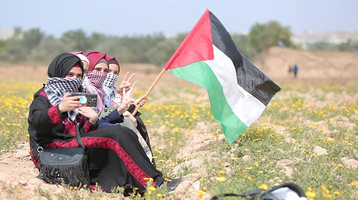 Three girls sitting in a field in Gaza Strip, raising Palestinian flag