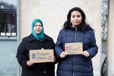 "Muna Luqman and Nisma Mansour holding ""Feminist peace"" signs"