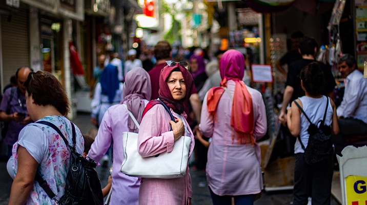 Turkish woman standing in the middle of a crowded street.