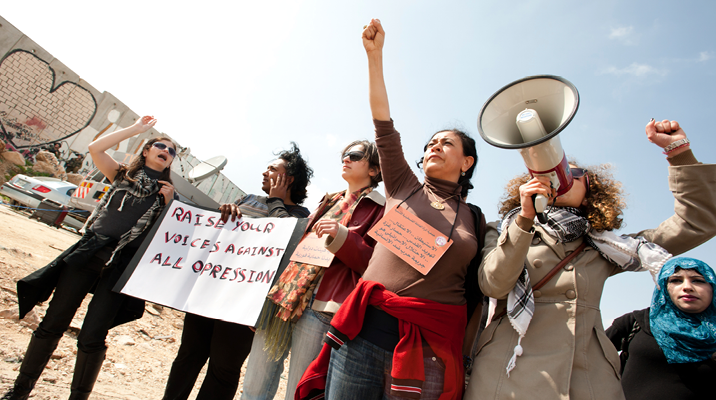 """Photo of six Arab women demonstrating, one holding a megaphone, and one holding a sign saying """"Raise you voices against oppression"""", one raising her fist up"""