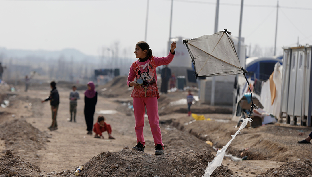 A displaced girl carries a kite at Khazer camp in Iraq.