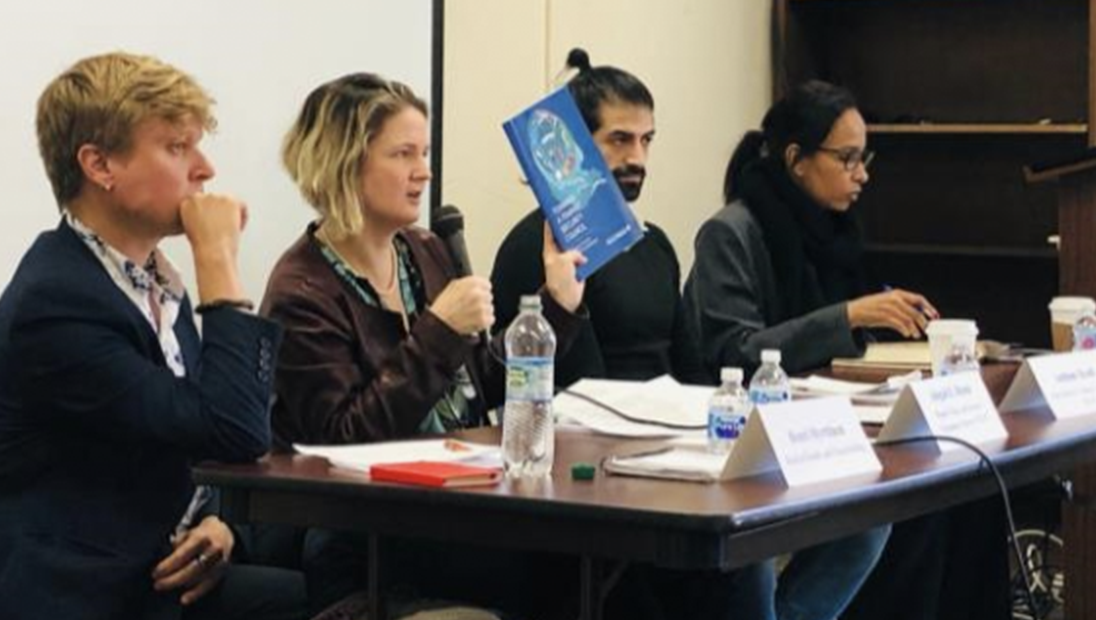 Two men and two women sitting at a panel table. One man is holding a booklet. One woman is speaking in a microphone