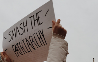 """Woman holding sign """"Smash the patriarchy"""""""